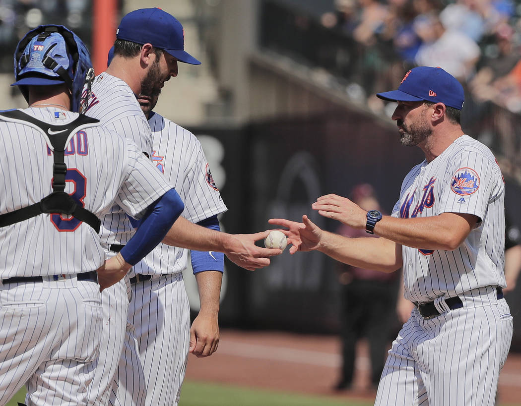 In this Thursday, May 3, 2018, file photo, New York Mets pitcher Matt Harvey, second from left, hands the ball to manager Mickey Callaway as he is relieved in the seventh inning of a baseball game ...