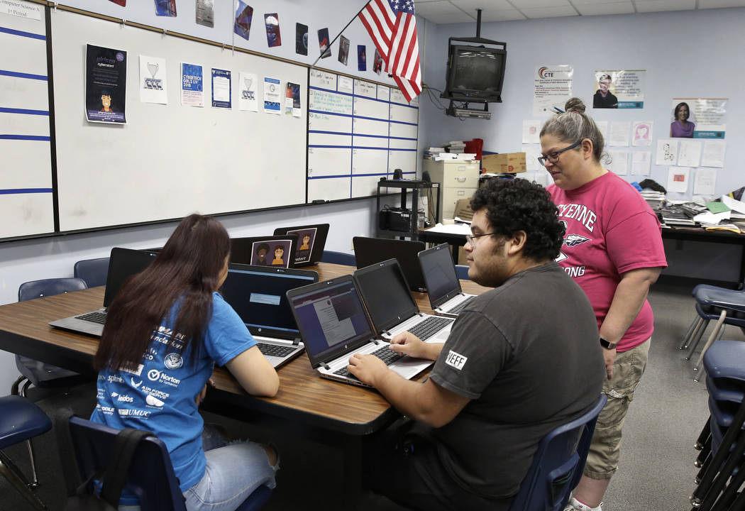 Fran Bromley-Norwood, a teacher at Cheyenne High School, checks 12th-grade student Ricardo Torres' and 11th-grade student Ivette Para's classwork during cyber defense class on Friday, May 18, 2018 ...