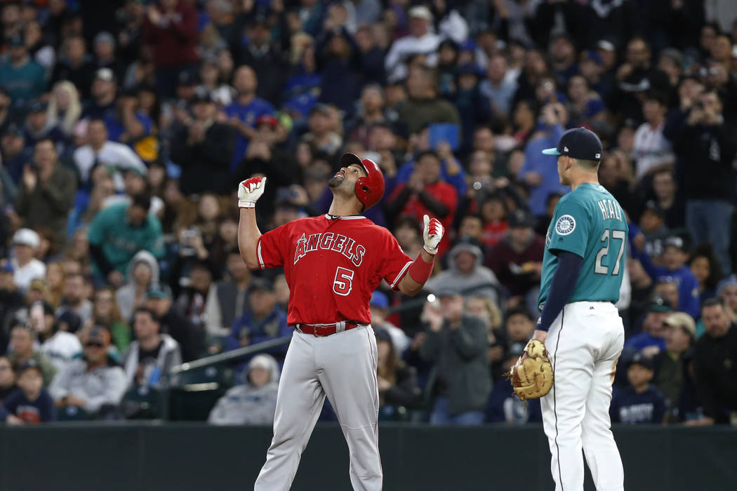Los Angeles Angels' Albert Pujols (5) celebrates as Seattle Mariners first baseman Ryon Healy watches after Pujols gets his 3,000th career hit, during the fifth inning of a baseball game Friday, M ...