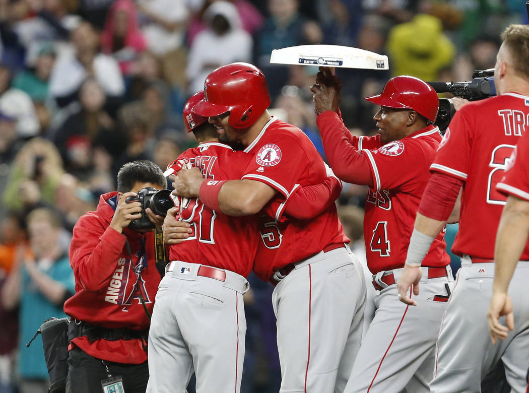 Los Angeles Angels' Albert Pujols, second from left, hugs third base coach Dino Ebel, left, while first base coach Alfredo Griffin carries first base, after Pujols singled for his 3,000th career h ...