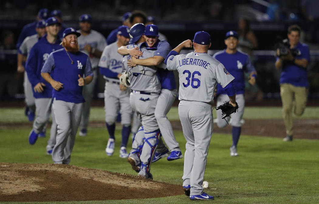 Los Angeles Dodgers relief pitcher Adam Liberatore clenches his fist as teammates run onto the field after the team's 4-0 win over the San Diego Padres in a baseball game in Monterrey, Mexico, Fri ...