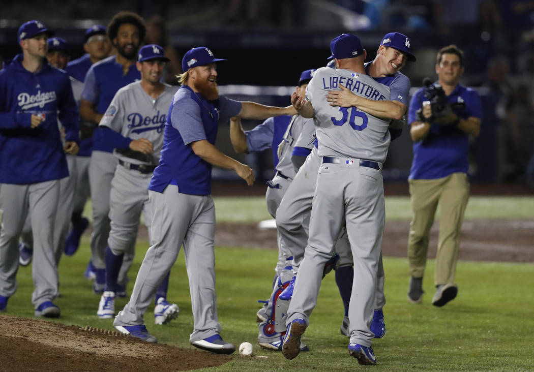 Los Angeles Dodgers relief pitcher Adam Liberatore is hugged by a teammate after the team's 4-0 win over the San Diego Padres in a baseball game in Monterrey, Mexico, Friday, May 4, 2018. (AP Pho ...