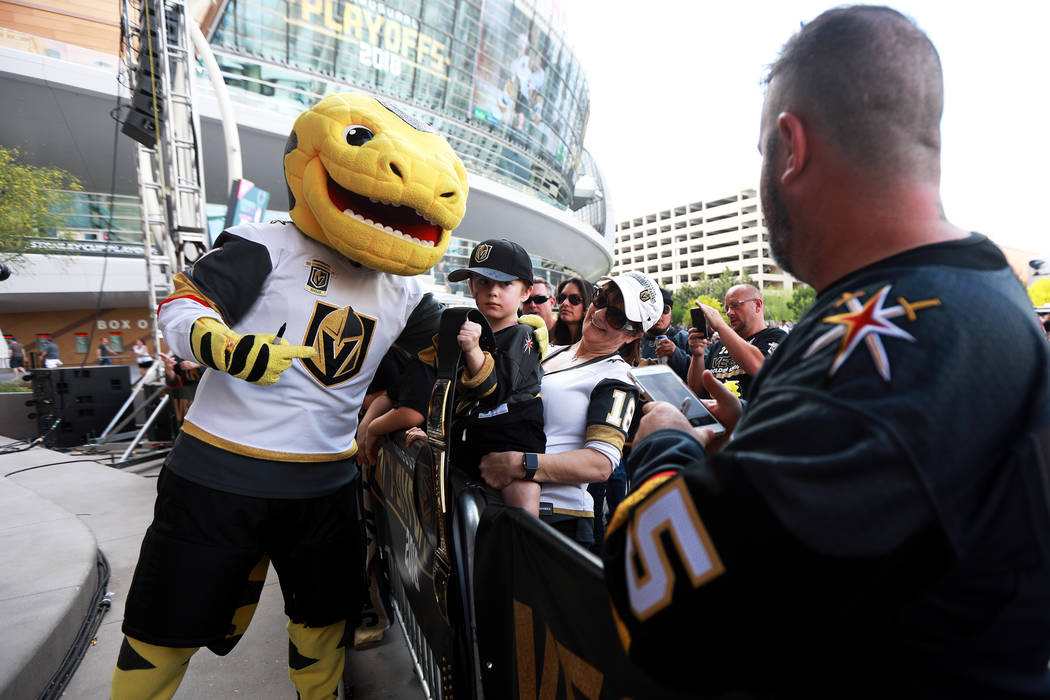 Cindy Blaylock and her 5-year-old grandson Hayden Schultz take a photo with Chance during a Vegas Golden Knights watch party for game six of the Stanley Cup playoffs outside on Toshiba Plaza in La ...