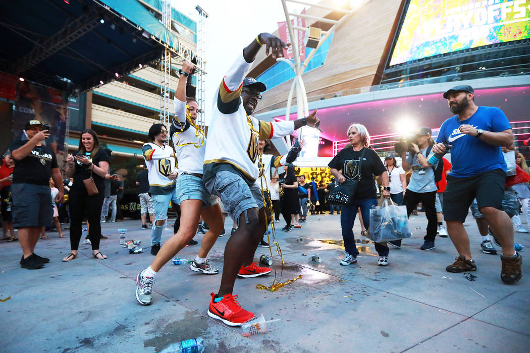 Brandi Giese, left, and Roger Hallback, both of Las Vegas, celebrate after the Vegas Golden Knights defeated the San Jose Sharks during a watch party for game six of the Stanley Cup playoffs outsi ...