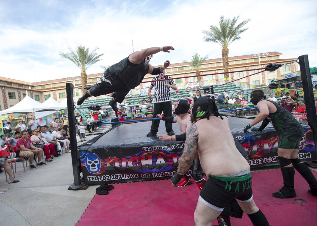 Luchador Tony Raze jumps from the ropes onto his opponents in a wrestling match during El Tiempo's Cinco de Mayo Fiesta at The Cannery in North Las Vegas, Saturday, May 5, 2018. Richard Brian Las ...