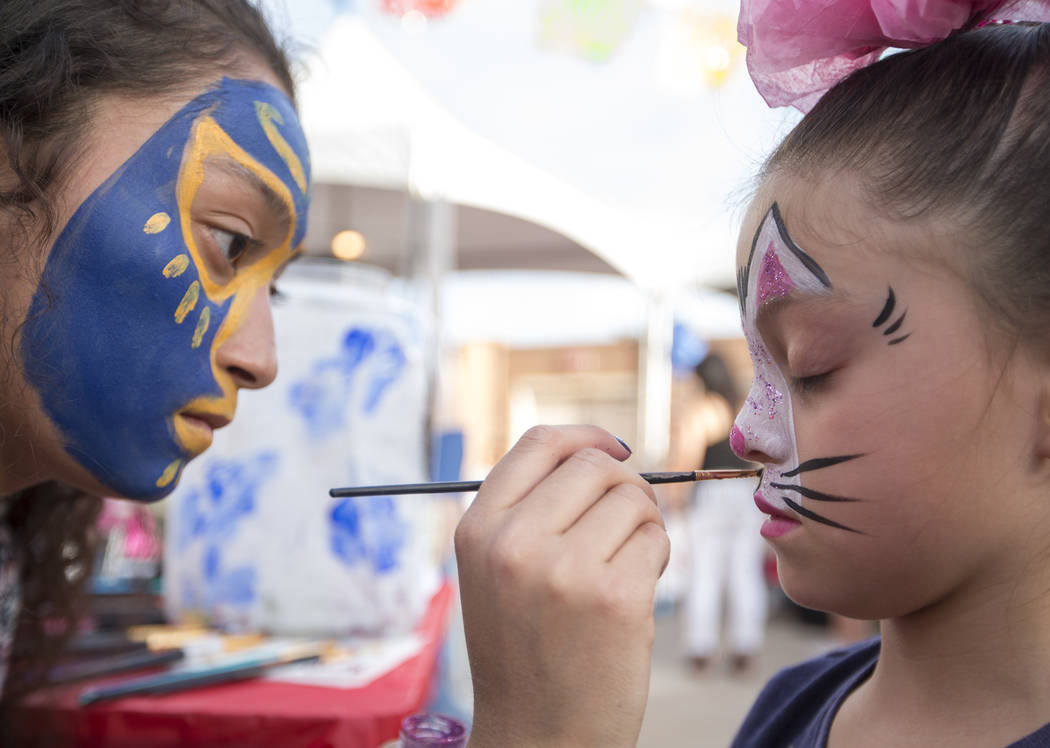 Las Vegas resident Zurisaday Becerra, 8, gets a bunny painted on her face by artist Carolina Mendez, of United Talents Face Painting, during El Tiempo's Cinco de Mayo Fiesta at The Cannery in Nort ...