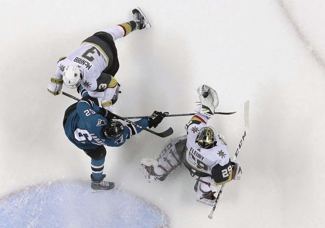 Vegas Golden Knights goaltender Marc-Andre Fleury, right, gloves the puck next to San Jose Sharks' Kevin Labanc, center, and Golden Knights defenseman Brayden McNabb (3) during the second period o ...