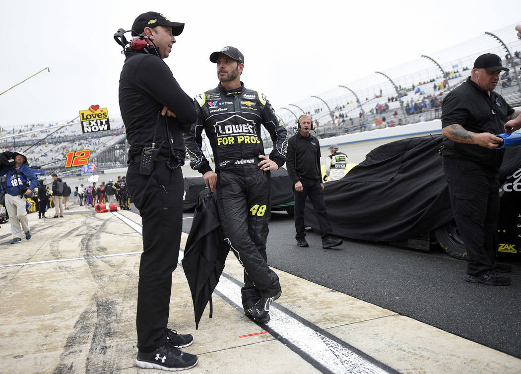 Jimmie Johnson, center, talks with crew chief Chad Knaus, left, during a weather delay in the NASCAR Cup series auto race, Sunday, May 6, 2018, at Dover International Speedway in Dover, Del. (AP P ...