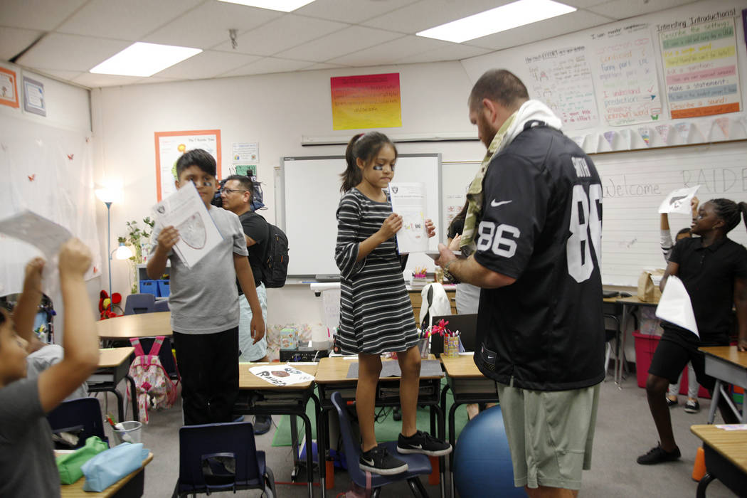 Oakland Raiders player Lee Smith looks at Ciara Guzman's, 10, drawing at Gene Ward elementary school in Las Vegas, Wednesday, May 9, 2018. Students participated in a raiders themed drawing contest ...