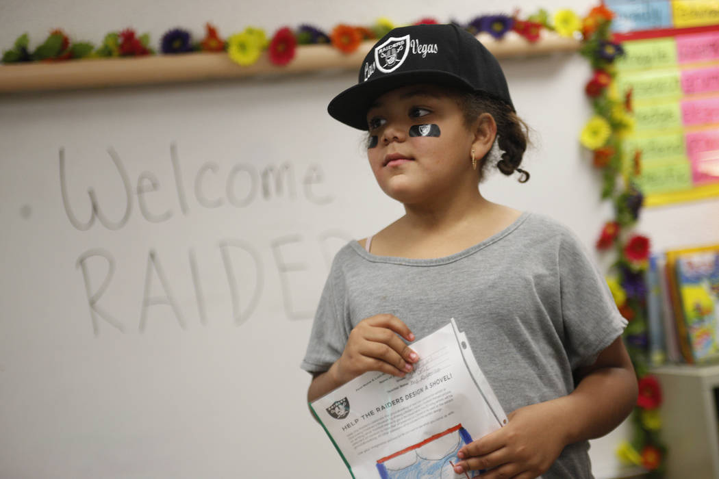 Jayda Mathis, 9, holds her drawing while watching Raiders players greet other students at Gene Ward elementary school in Las Vegas, Wednesday, May 9, 2018. Students participated in a raiders theme ...