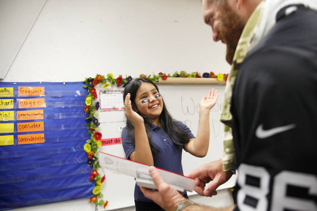 Ashley Ojeda Flores, 9, talks to Raiders player Lee Smith about her drawing at Gene Ward elementary school in Las Vegas, Wednesday, May 9, 2018. Students participated in a raiders themed drawing c ...