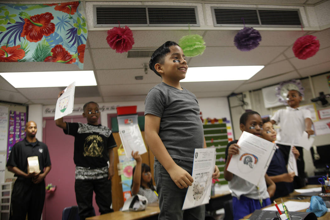 Marrail Parker-Briggs, 9, from left, Mauricio Garnica Mendez, 9, and Bryce Fortune, 8, wait with their drawings to show the Raiders players at Gene Ward elementary school in Las Vegas, Wednesday, ...