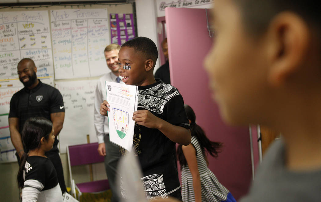 Marrail Parker-Briggs, 9, left, and Bryce Fortune, 8, right, hold their drawings to show the Raiders players at Gene Ward elementary school in Las Vegas, Wednesday, May 9, 2018. Students participa ...