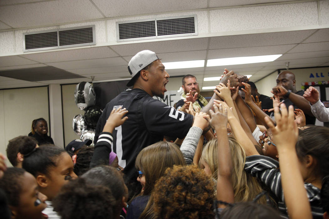 Oakland Raiders player Bruce Irvin huddles with students at Gene Ward elementary school in Las Vegas, Wednesday, May 9, 2018. Students participated in a raiders themed drawing contest. Rachel Asto ...