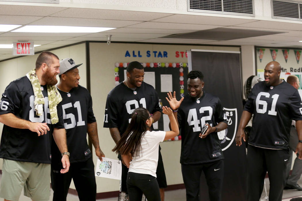 Oakland Raider player Karl Joseph high fives winner Guadalupe Galicia Hernandez, 9, as his fellow players Lee Smith, from left, Bruce Irvin, Shilique Calhoun, and Rodney Hudson look on at Gene W ...