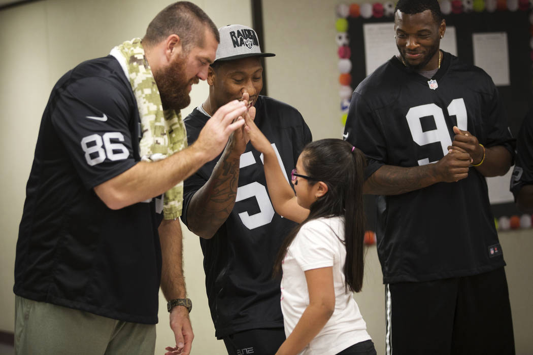 Oakland Raiders players Lee Smith, from left, Bruce Irvin, and Shilique Calhoun congratulate Guadalupe Galicia Hernandez, 9, who won a raiders themed drawing contest at Gene Ward elementary school ...