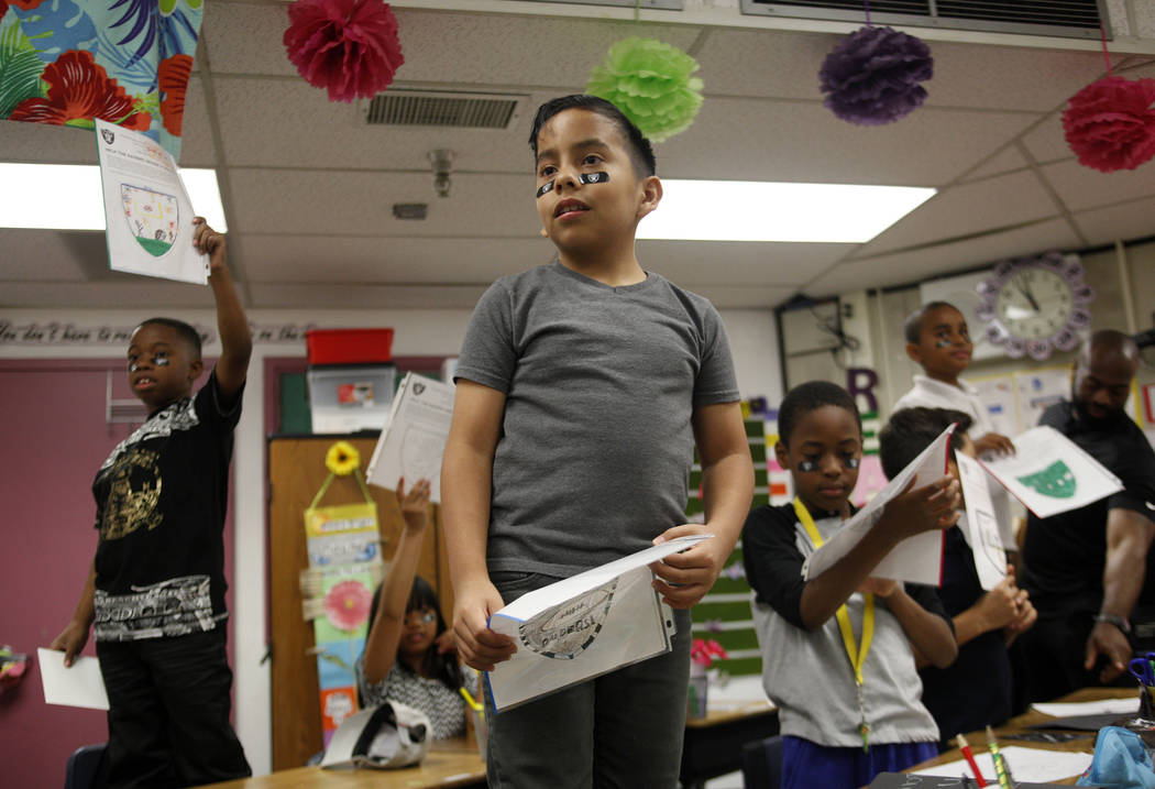 Marrail Parker-Briggs, 9, from left, Mauricio Garnica Mendez, 9, and Bryce Fortune, 8, wait with their raiders themed drawings to show the players at Gene Ward elementary school in Las Vegas, Wedn ...