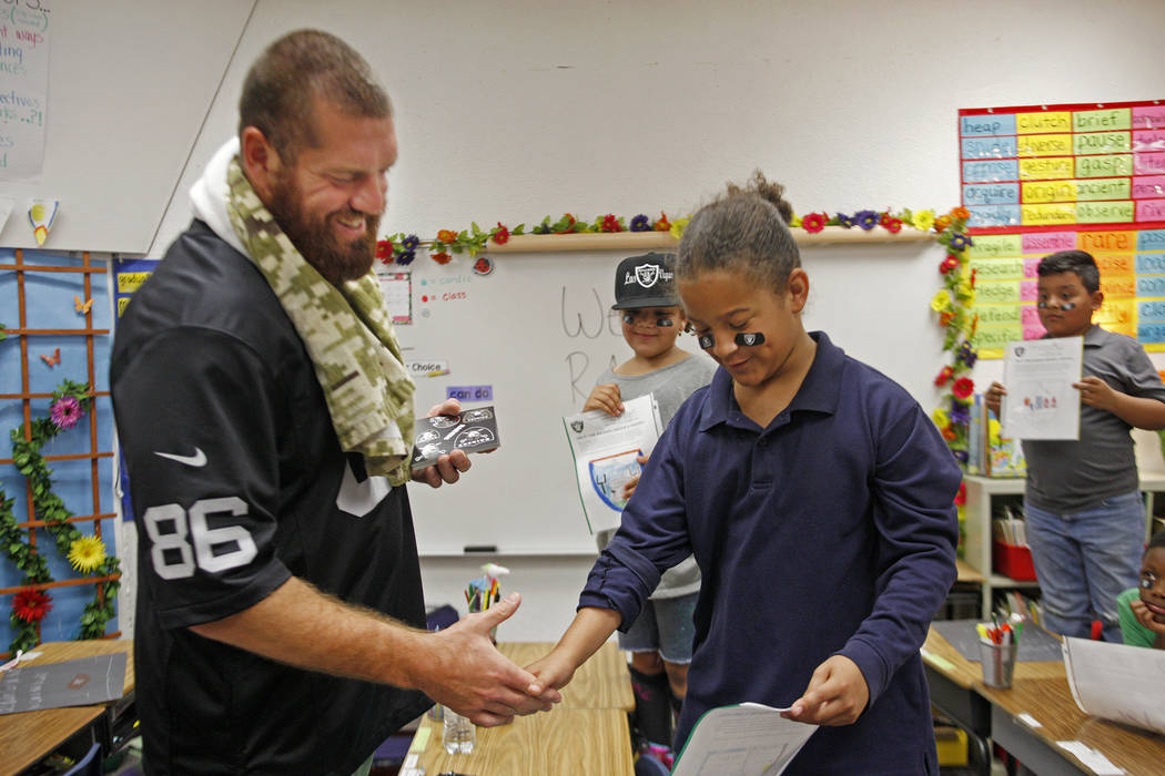 Oakland Raiders player Lee Smith talks to Royalty Edwards, 9, at Gene Ward elementary school in Las Vegas, Wednesday, May 9, 2018. Students participated in a raiders themed drawing contest. Rachel ...
