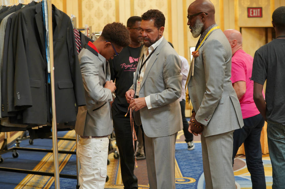 A student get a little help trying on a suit from Las Vegas entertainer Clint Holmes, center, who performs at the Westgate.