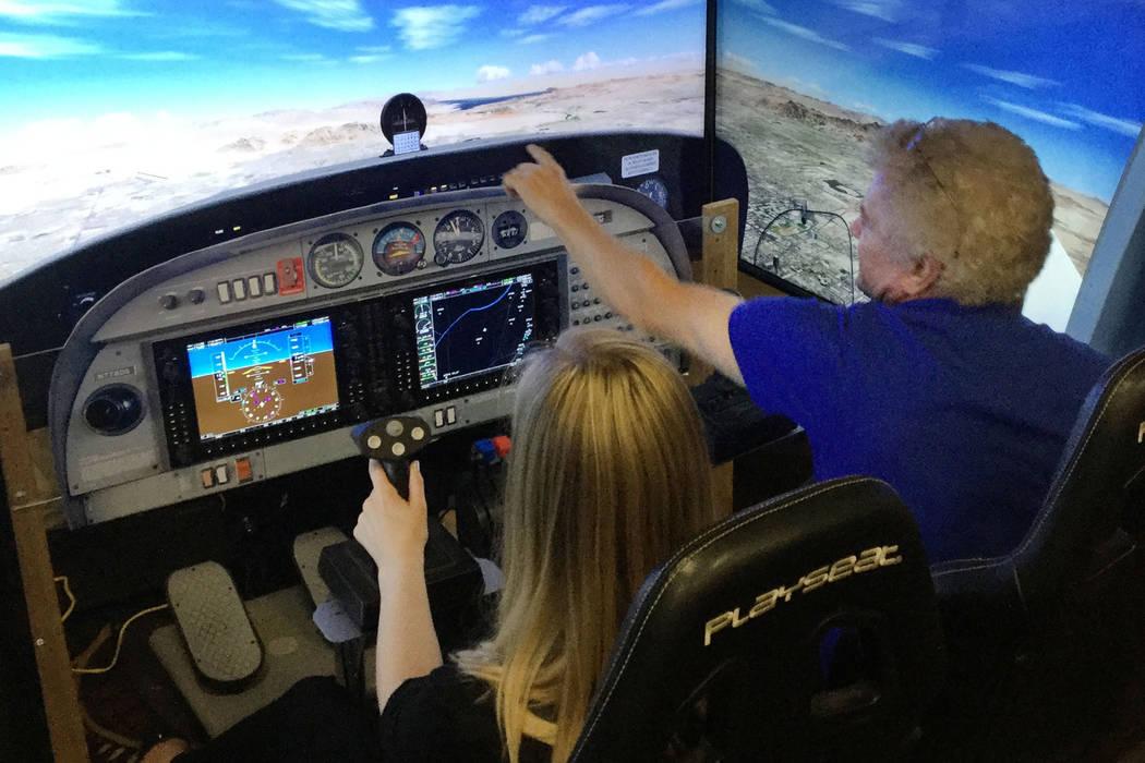Katlyn Flaherty, a human resource coordinator at Atlas Air, flies in a simulator with FAPA volunteer Peter Forman. (Bailey Schulz/Review-Journal)