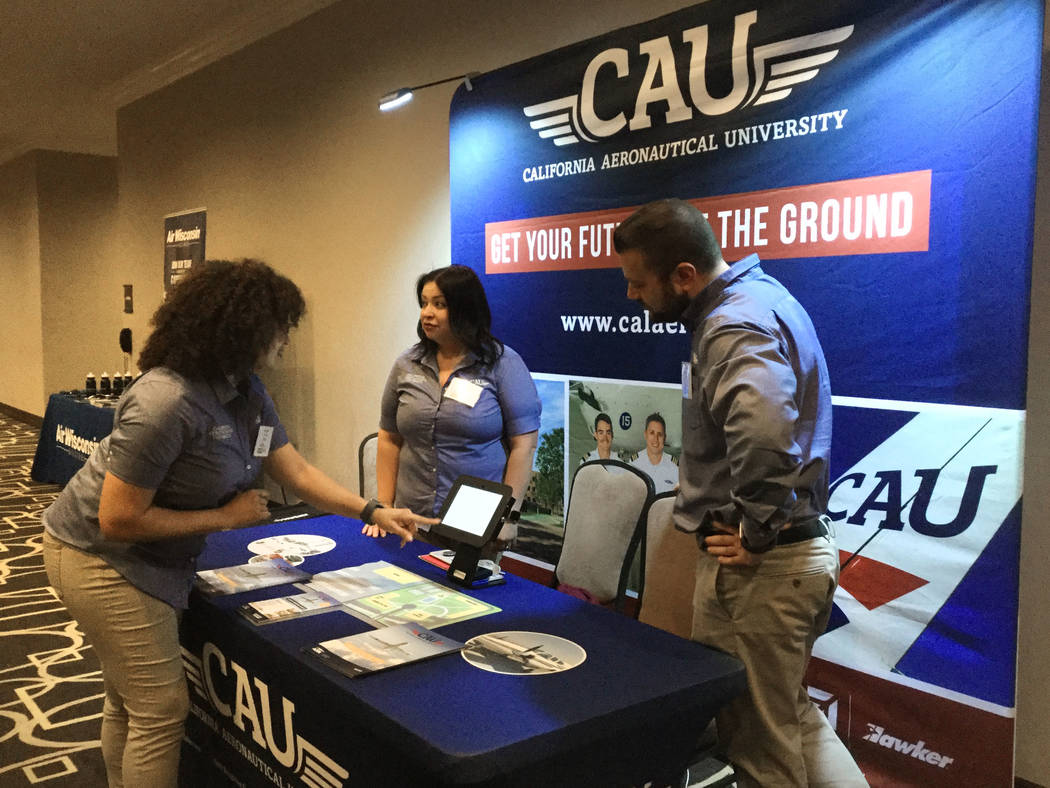 Adia Smith, Susy Rodriguez and Max Ovsovich stand near the California Aeronautical University booth at the Future and Active Pilot Advisors Future Pilot Program on May 2. (Bailey Schulz/Review-Jou ...