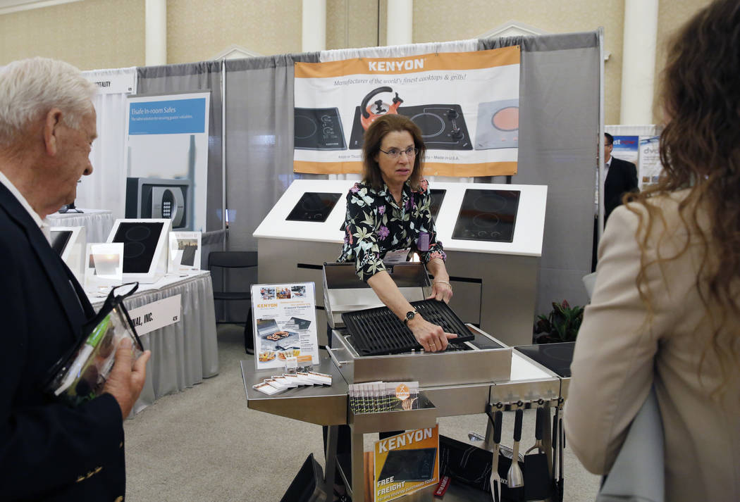 Suzanne Owens, vice president sales of KENYON, demonstrates how to grill on all season portable grill during the annual convention from the American Resort Development Association at Caesars Palac ...