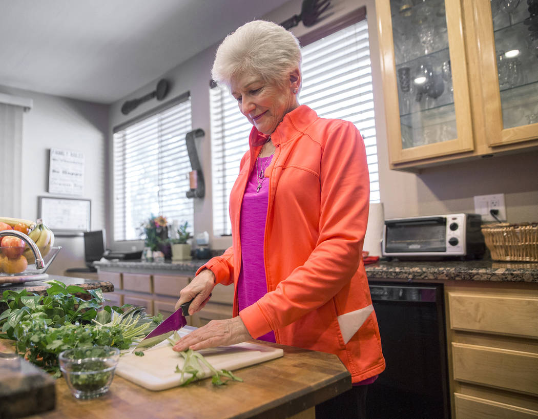 Writer/advocate Nancy Nelson, 74, cuts fresh vegetables for chicken soup at her home in Las Vegas. Nelson was diagnosed with early-onset Alzheimer's disease in 2013 and attributes much of her cont ...