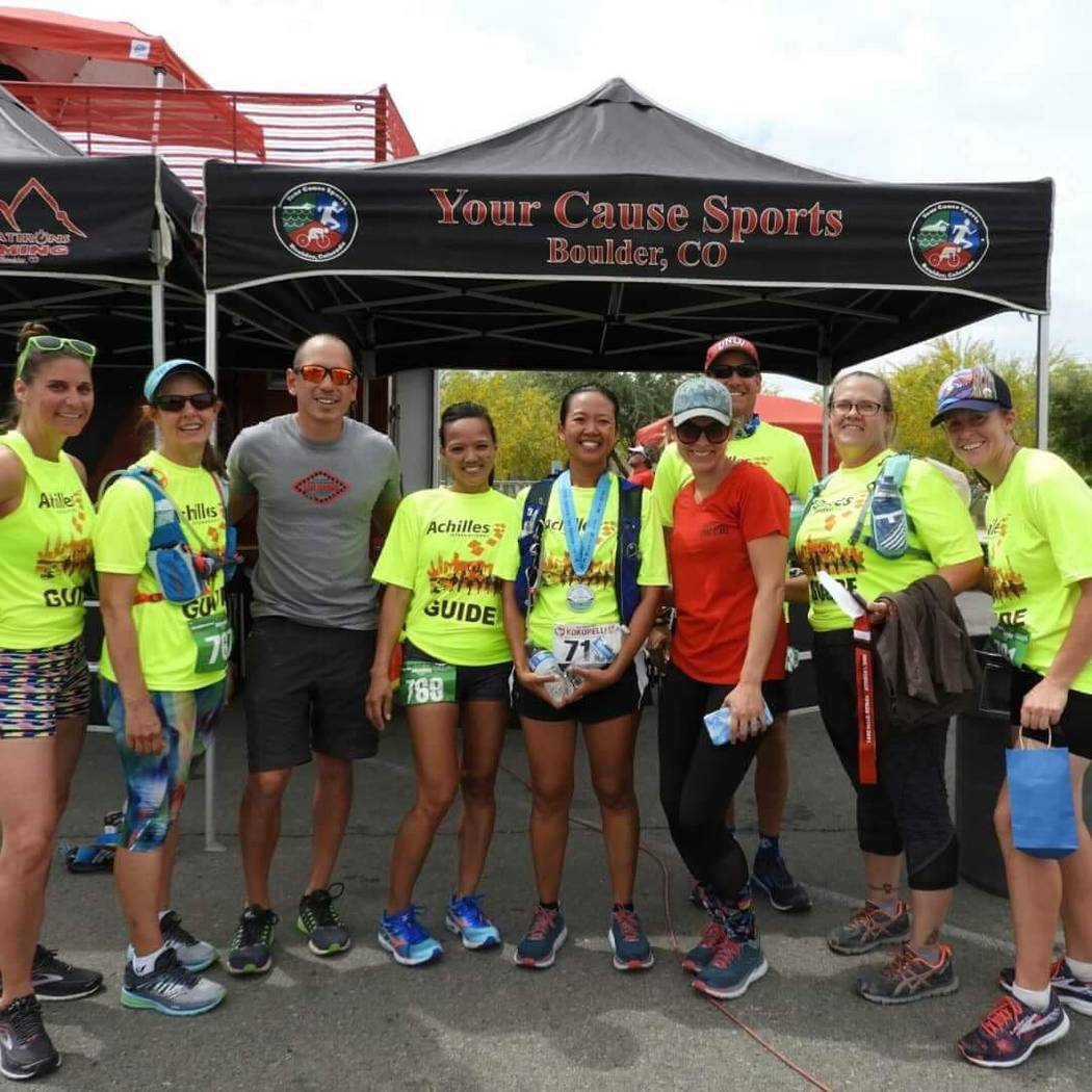 Terri Rupp, center, president of the National Federation of the Blind of Nevada, wears a medal after competing in a recent race. Achilles International assists visually impaired runners in their e ...
