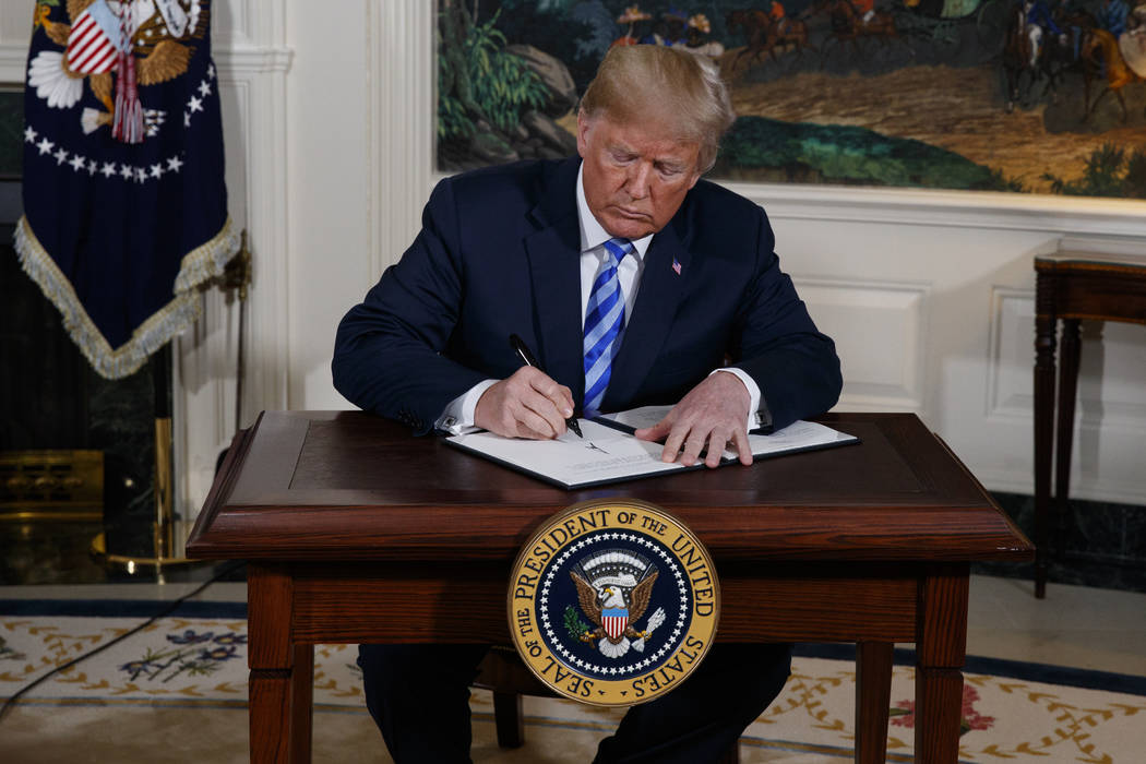 President Donald Trump signs a Presidential Memorandum on the Iran nuclear deal from the Diplomatic Reception Room of the White House, Tuesday, May 8, 2018, in Washington. (AP Photo/Evan Vucci)