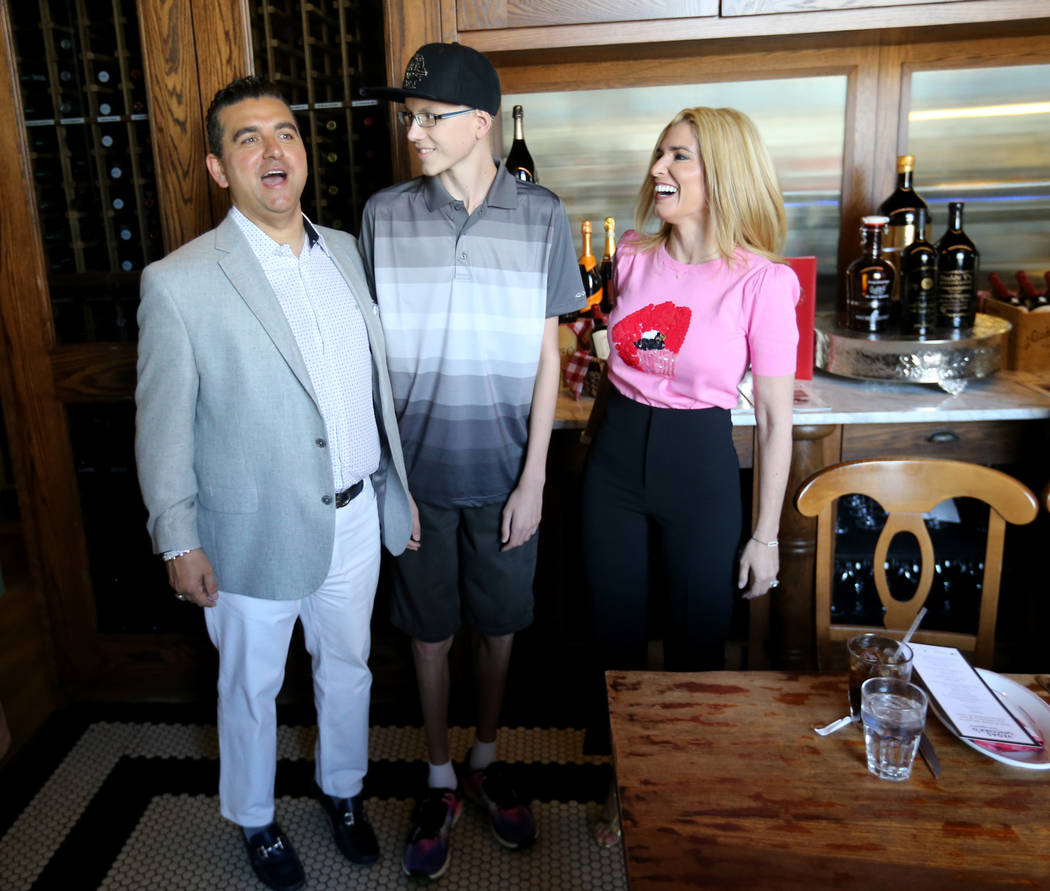 Buddy Valastro, left, tries to be as tall as Michael Laliberte, 14, of Canada as Valastro's wife Lisa looks on at Buddy V's Ristorante at The Venetian during Vegas Uncork'd Friday, May 11, 2018. K ...
