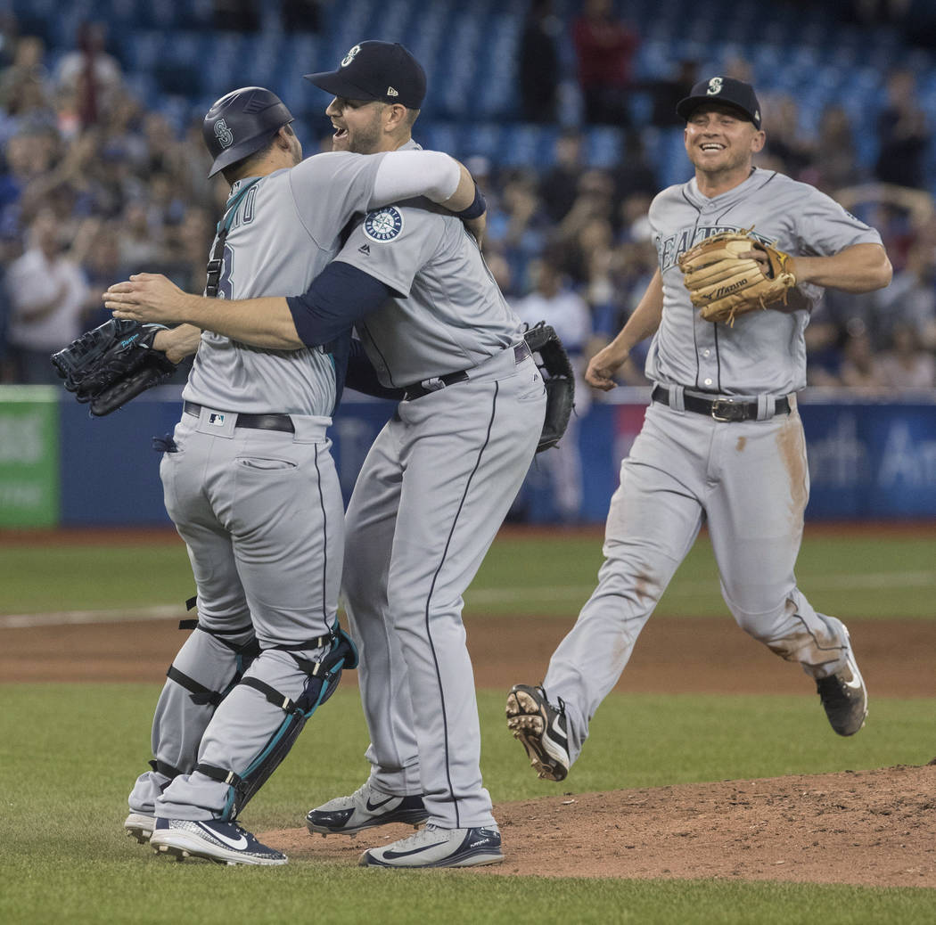 Seattle Mariners starting pitcher James Paxton, center, celebrates with teammates after throwing a no-hitter against the Toronto Blue Jays in a baseball game Tuesday, May 8, 2018, in Toronto. (Fre ...