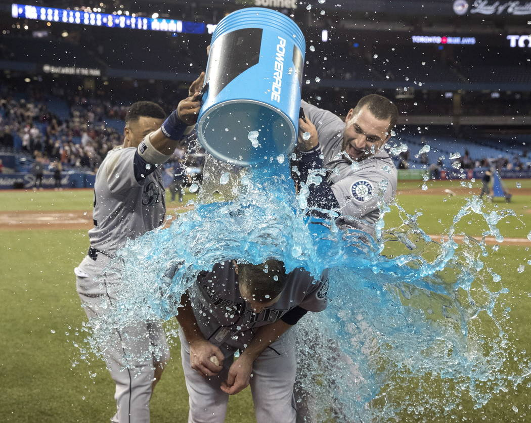 Seattle Mariners starting pitcher James Paxton is doused by teammates Robinson Cano and Mike Zunino after he pitched a no-hitter against the Toronto Blue Jays in a baseball game Tuesday, May 8, 20 ...