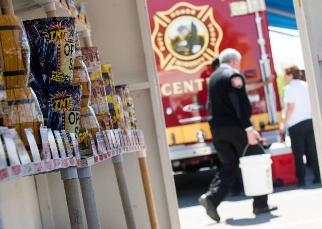 Las Vegas Fire Department spokesman Tim Szymanski carries a bucket of water Wednesday for a fireworks demonstration near a makeshift fireworks stand at Las Vegas Fire and Rescue headquarters.