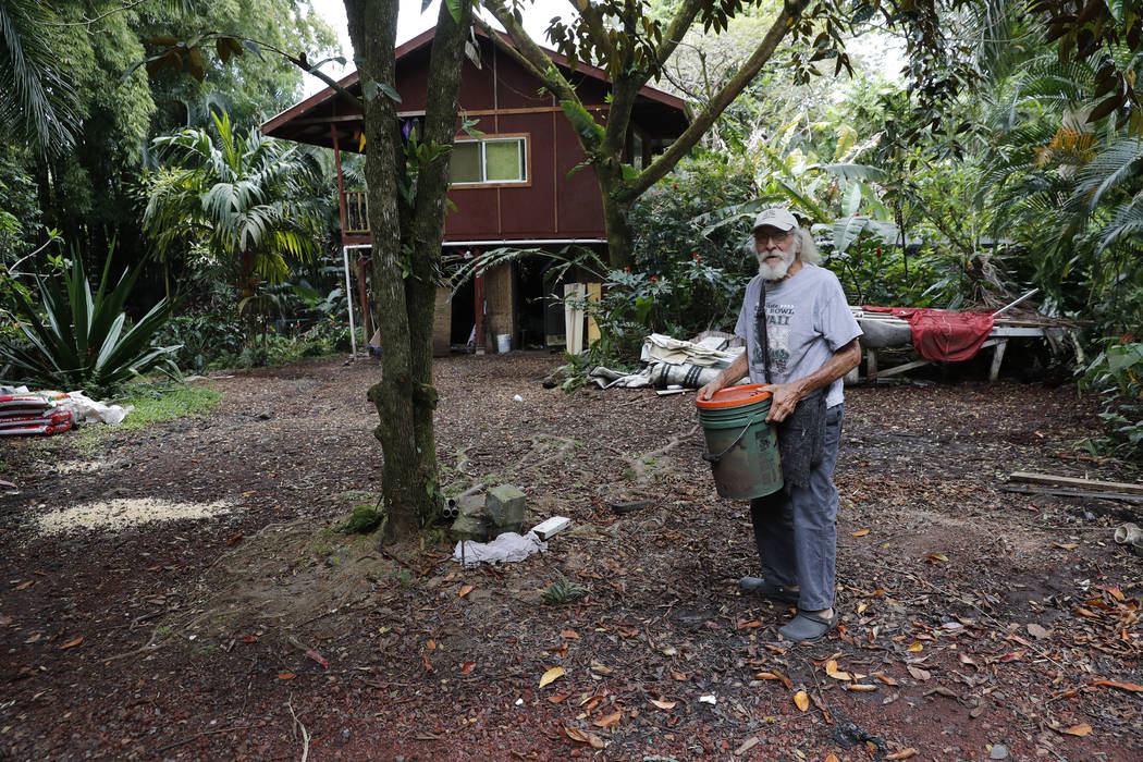 In this Saturday, May 5, 2018, photo, Edwin Montoya, 76, carries a bucket on his family's property near Pahoa, Hawaii. Just a couple of miles up the hill, lava has been gushing from the ground and ...