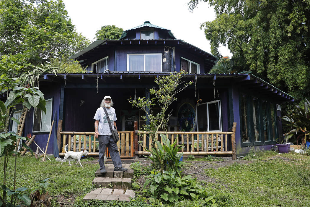 In this Saturday, May 5, 2018, photo, Edwin Montoya, 76, poses for a photo outside his home near Pahoa, Hawaii. Just a couple of miles up the hill, lava has been gushing from the ground and destro ...