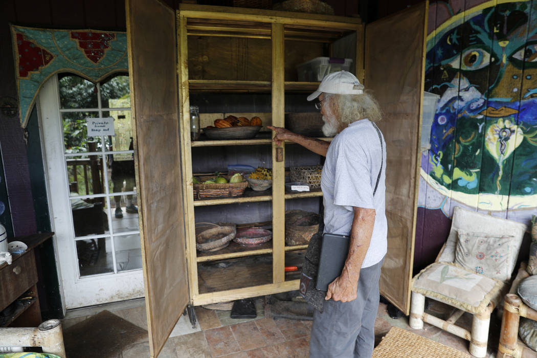In this Saturday, May 5, 2018, photo, Edwin Montoya, 76, looks at fruit in the pantry on his family's property near Pahoa, Hawaii. Just a couple of miles up the hill, lava has been gushing from th ...