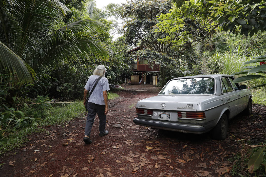 In this Saturday, May 5, 2018, photo, Edwin Montoya, 76, walks on his family's property near Pahoa, Hawaii. Just a couple of miles up the hill, lava has been gushing from the ground and destroying ...