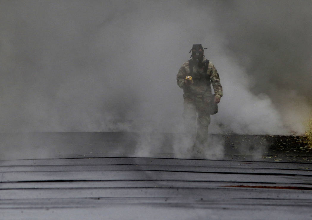 First Lt. Aaron Hew Len, of the U.S. National Guard, tests air quality near cracks that are emitting toxic gasses from a lava flow in the Leilani Estates subdivision near Pahoa, Hawaii, Tuesday, M ...