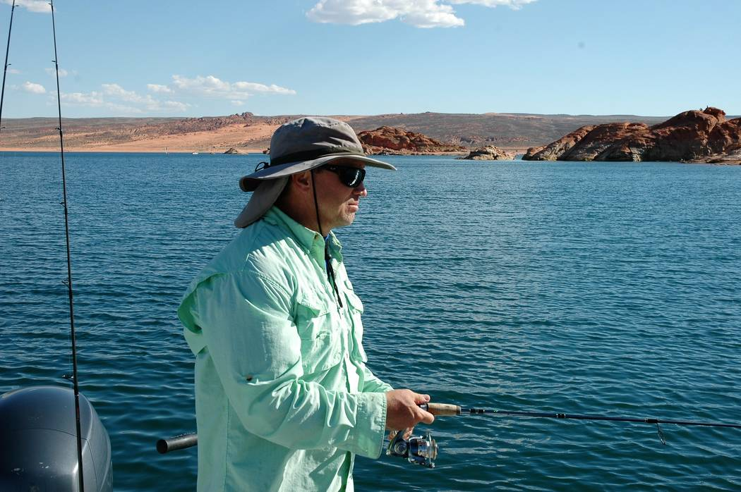 Roger Williams, of Las Vegas, fishes for largemouth bass at Utah's Sand Hollow reservoir. The desert sandstone provides a striking color contrast to that of the reservoir's blue water. (Doug Nielsen)