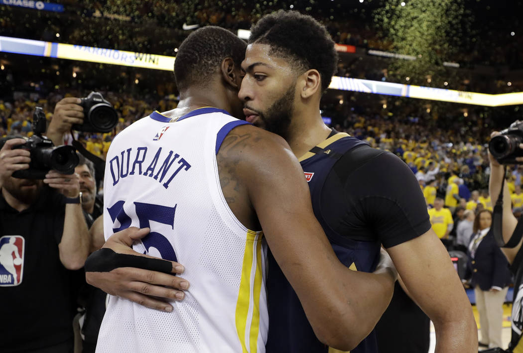 New Orleans Pelicans' Anthony Davis, right, is hugged by Golden State Warriors' Kevin Durant at the end of Game 5 of an NBA basketball second-round playoff series Tuesday, May 8, 2018, in Oakland, ...