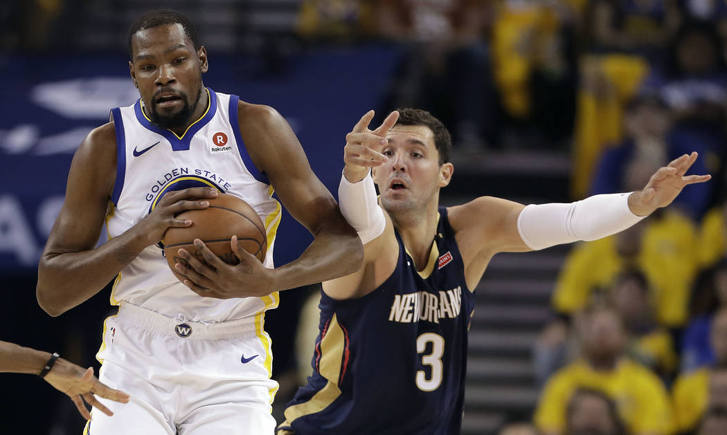 Golden State Warriors' Kevin Durant, left, is defended by New Orleans Pelicans' Nikola Mirotic during the first half in Game 5 of an NBA basketball second-round playoff series Tuesday, May 8, 2018 ...