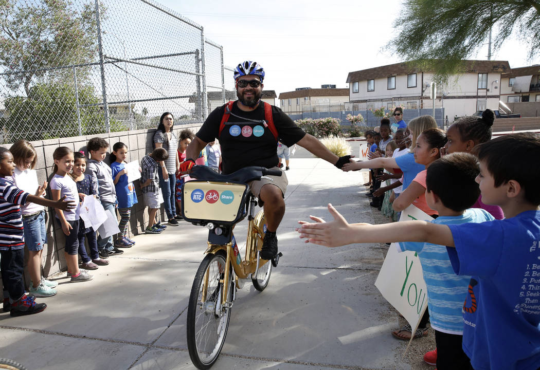 """Students at Robert L. Taylor Elementary School greet Matthew Chavez as he delivers books to their school during the eighth annual """"Ride for Reading"""" event on Friday, May 11, 2018, in Henderson ..."""