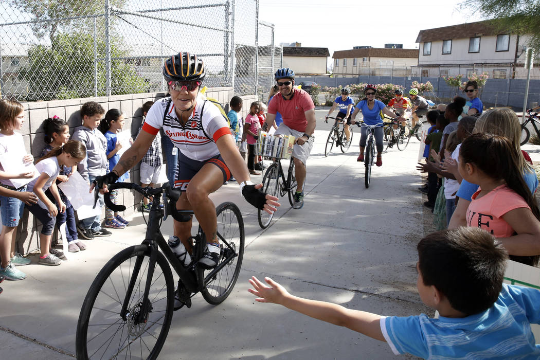 Students at Robert L. Taylor Elementary School greet bicyclists who deliver books to their school arrive during the eighth annual ÒRide for ReadingÓ event on Friday, May 11, 2018, in Hen ...