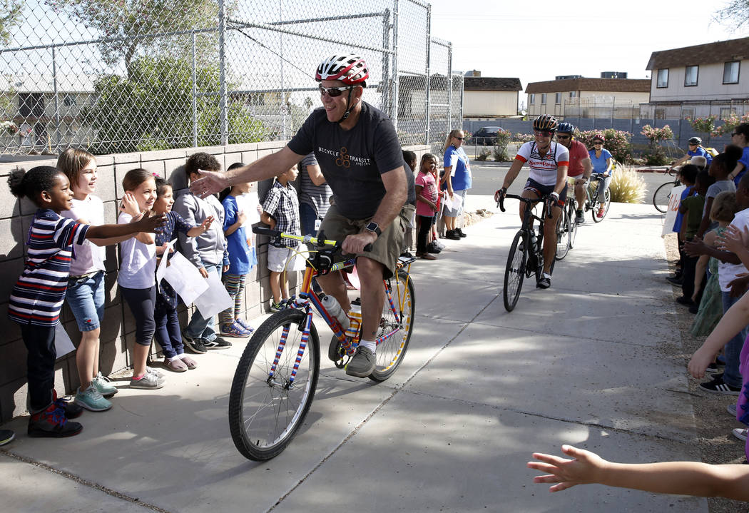 """Students at Robert L. Taylor Elementary School greet bicyclists who deliver books to their school arrive during the eighth annual """"Ride for Reading"""" event on Friday, May 11, 2018, in ..."""