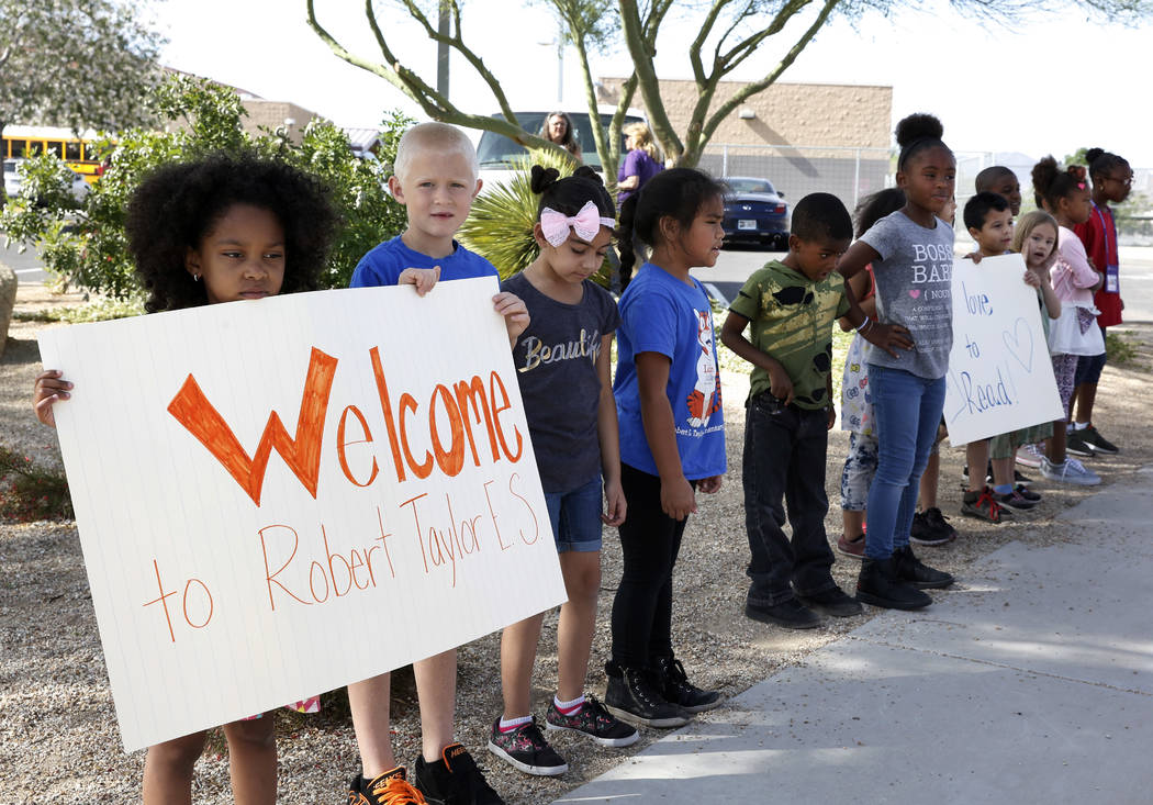 Students at Robert L. Taylor Elementary School, including Mykell Cannoa, left, 7, and Cayden Bunevitch, 7, are waiting to greet bicyclists who deliver books to their school during the eighth annua ...
