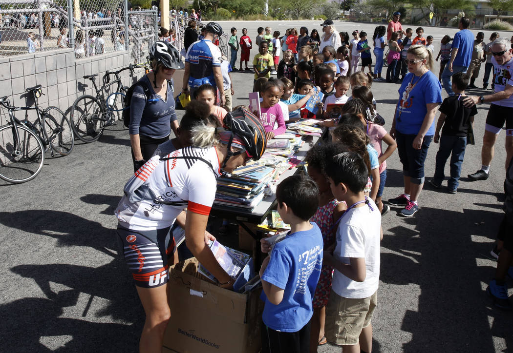 """Kristie Peressini, left, helps Robert L. Taylor Elementary School students select their books during the eighth annual """"Ride for Reading"""" event on Friday, May 11, 2018, in Henderson. ..."""