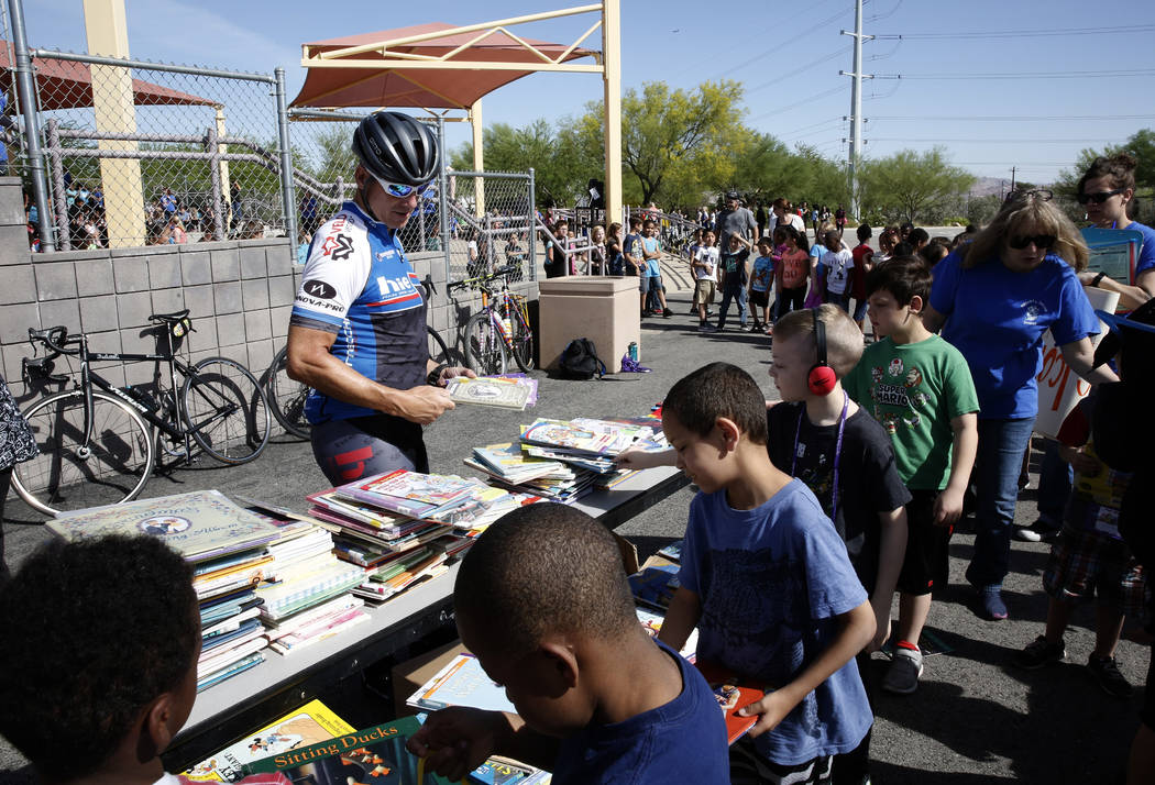 """Mark Greenberg, left, watches as Robert L. Taylor Elementary School students select their books during the eighth annual """"Ride for Reading"""" event on Friday, May 11, 2018, in Henderso ..."""