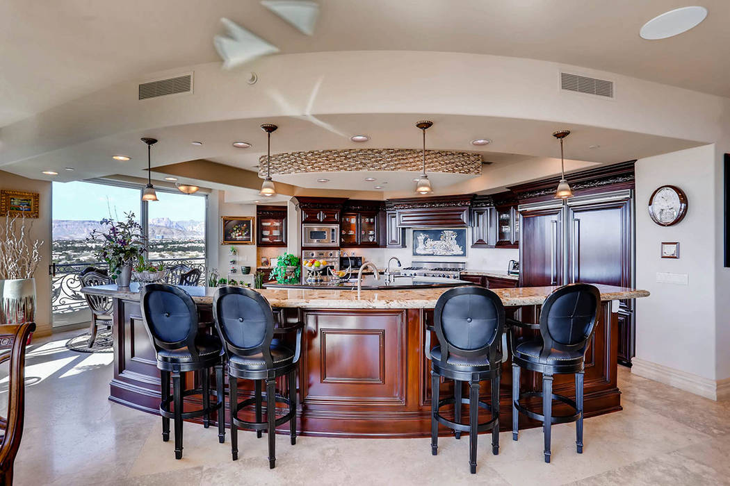 The kitchen features a large island with seating. (Char Luxury Real Estate)