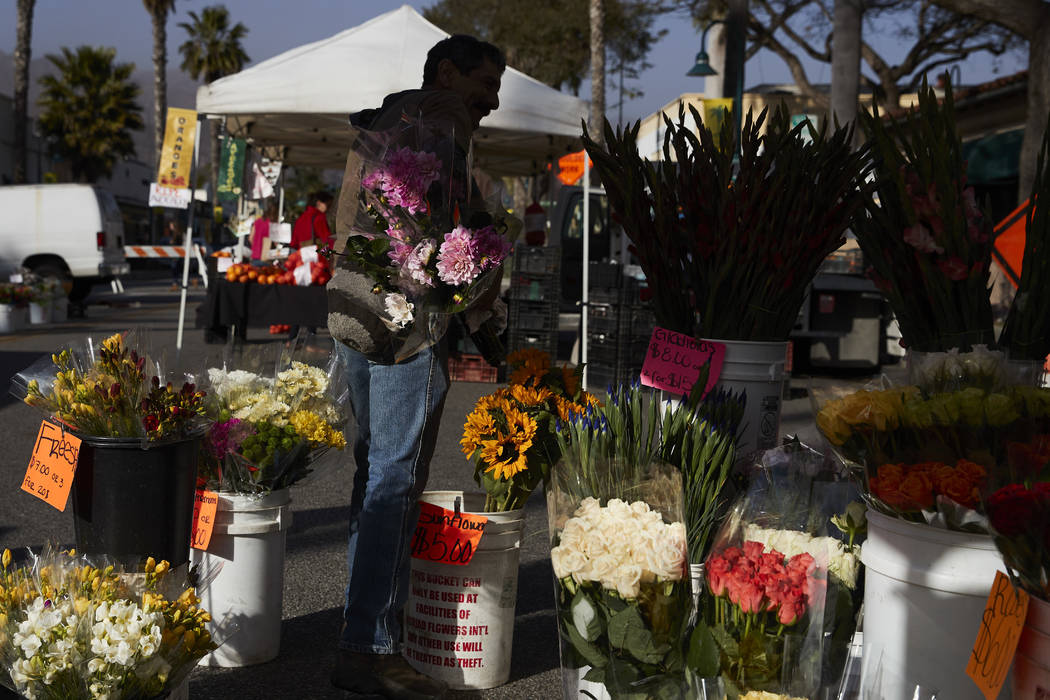 In this Thursday, April 12, 2018, photo, a man buys locally grown flowers at a farmers' market in Carpinteria, Calif. Residents of Carpinteria say they feel lucky to live in what they consider a s ...