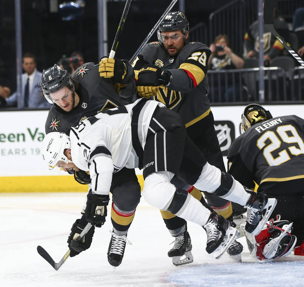 Los Angeles Kings center Trevor Lewis (22) gets taken down by Golden Knights defenseman Colin Miller (6) during the second period of Game 1 of an NHL hockey first-round playoff series at T-Mobile ...